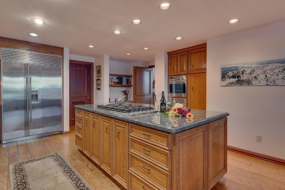 Another kitchen with a large rectangular center island featuring a granite countertop. Images courtesy of Toptenrealestatedeals.com.