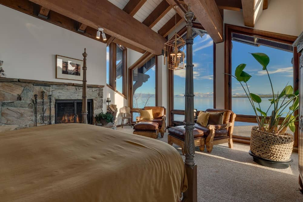 A bedroom suite featuring a large cozy bed and a stone fireplace on the side. There's a sitting area near the windows too. Images courtesy of Toptenrealestatedeals.com.