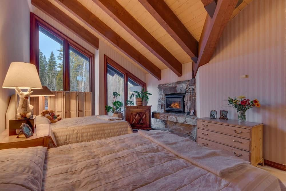 A guests bedroom sutie with two bed sets lighted by table lamps. The room has a stone fireplace and a wooden shed ceiling with exposed beams. Images courtesy of Toptenrealestatedeals.com.