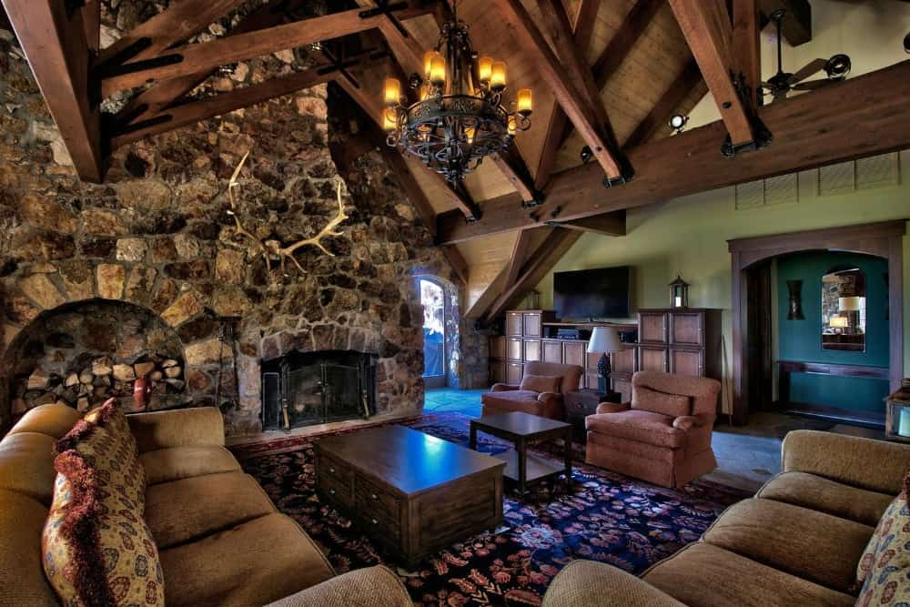 This living space boasts large couches and a stone fireplace set under the home's wooden ceiling with exposed wooden beams. Images courtesy of Toptenrealestatedeals.com.