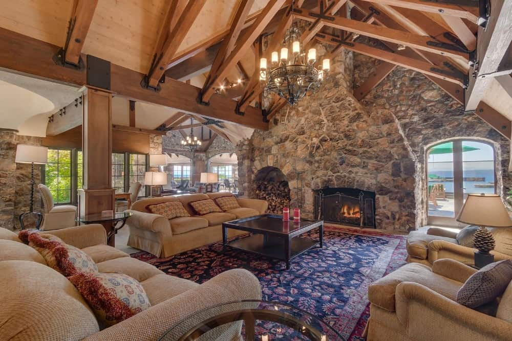 Large formal living room with a set of classy couches and a large area rug, along with a large stone fireplace. Images courtesy of Toptenrealestatedeals.com.