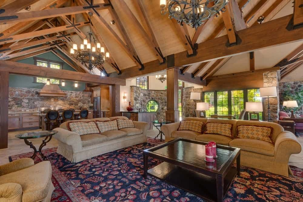 Large great room with classy couches and other seats under the home's tall wooden vaulted ceiling with exposed beams. Images courtesy of Toptenrealestatedeals.com.