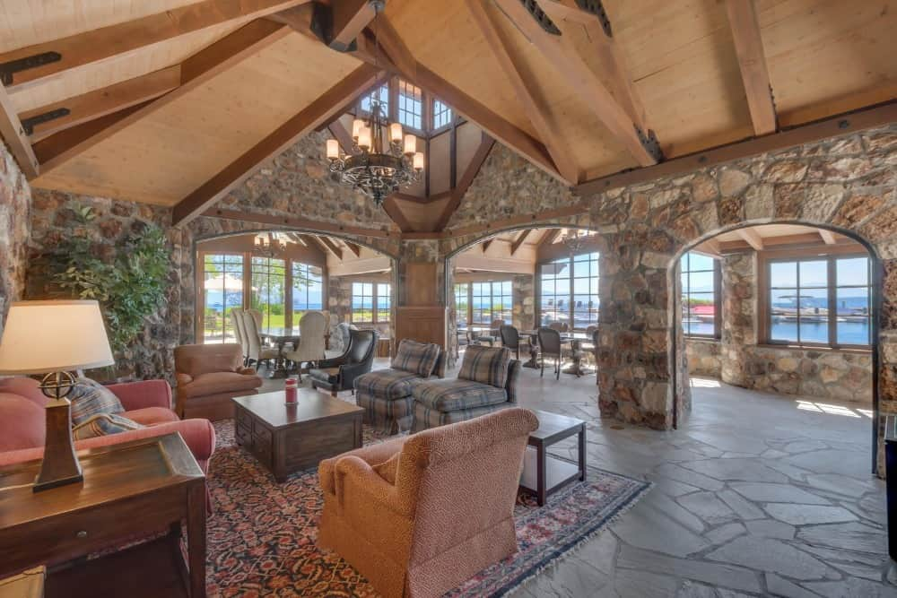 A large great room with a nice set of seats on top of an area rug, set on a custom ceiling with wooden beams. Images courtesy of Toptenrealestatedeals.com.