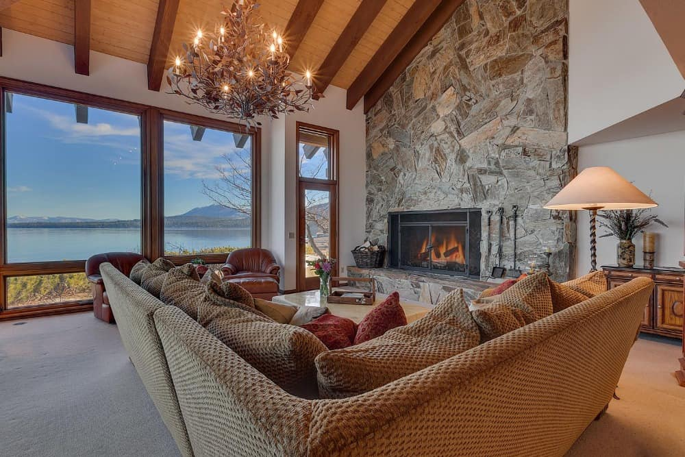 This living space offers a luxurious, large and comfy sofa along with a large stone fireplace. The area is lighted by a stunning and glamorous chandelier. Images courtesy of Toptenrealestatedeals.com.