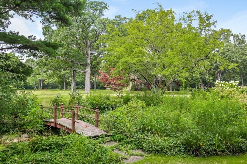 The garden boasts a lush greenery and well-maintained lawn area, along with this bridge that looks absolutely lovely. Images courtesy of Toptenrealestatedeals.com.
