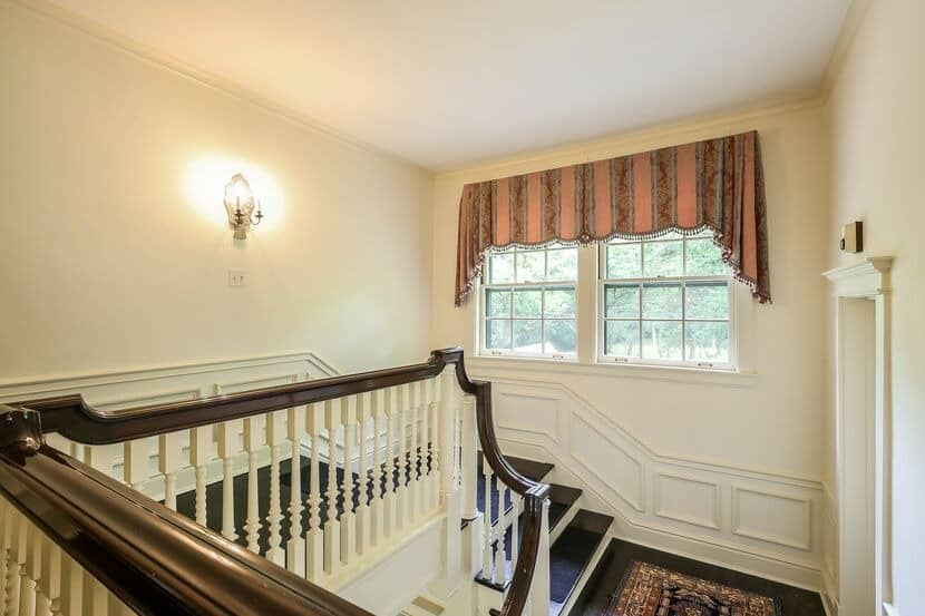 Here's the home's staircase featuring dark hardwood steps and handrails, along with white railings. Images courtesy of Toptenrealestatedeals.com.