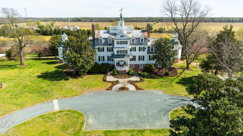 Aerial view of this historic Virginia home boasting its magnificent exterior and the wide lawn area and gorgeous driveway.