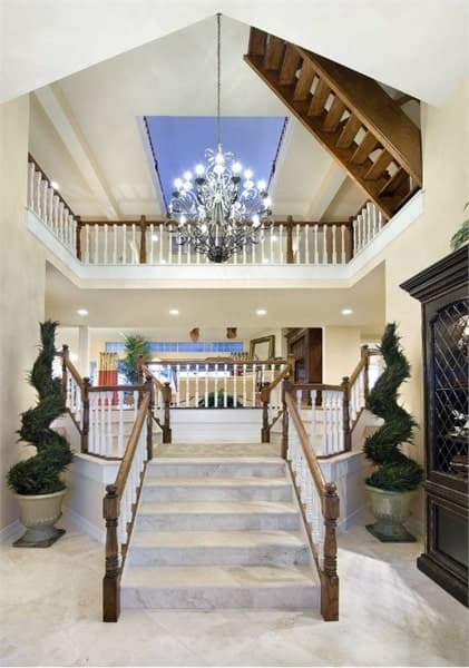The foyer has a soaring ceiling and a magnificent bifurcated staircase lit by a grand chandelier.