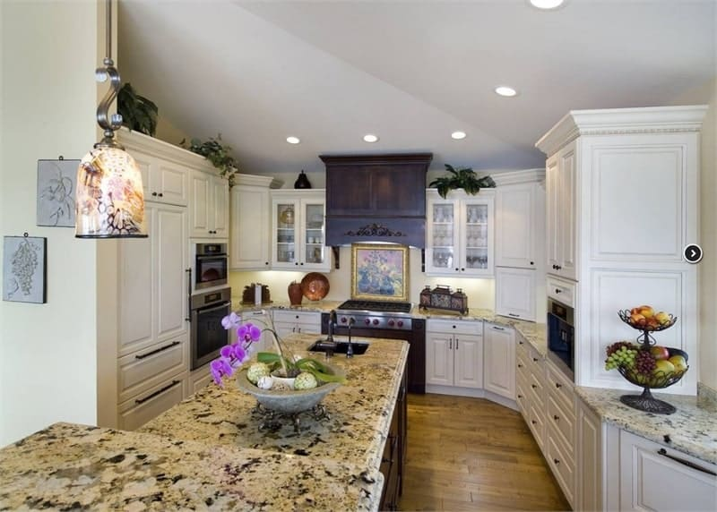 The kitchen offers white cabinetry and a two-tier island bar fitted with an undermount sink.