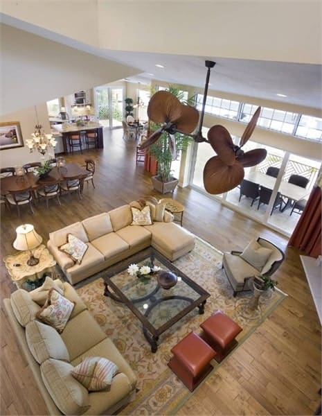 Top view of the living room with beige sectionals, gray armchair, and a pair of leather stools surrounding the glass coffee table.