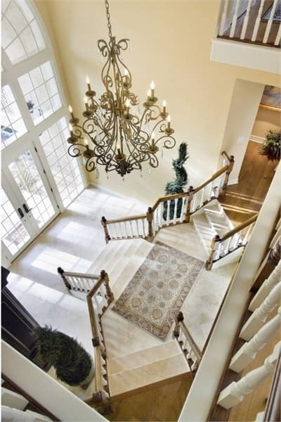 View of the foyer and staircase from the balcony showing the ornate chandelier and a classic rug that lays on the marble landing.