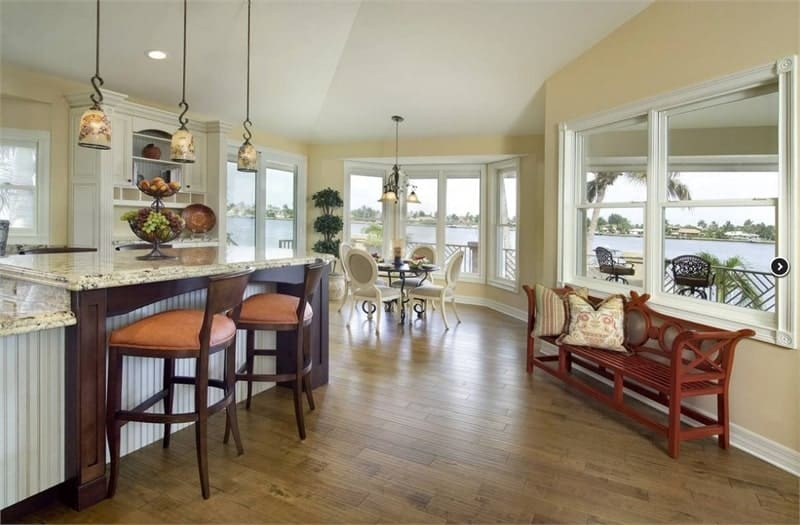 Kitchen with a sitting area and a breakfast nook surrounded by white framed windows that bring natural light in.