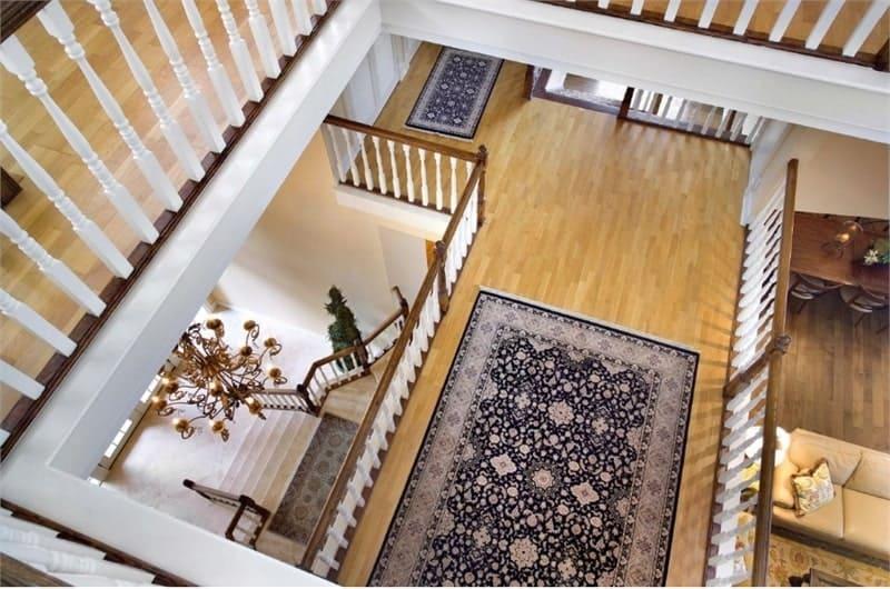 Second-floor walkway with hardwood flooring topped by black printed rugs.