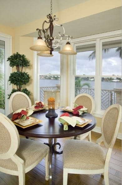 A closer look at the breakfast nook shows the dark wood table and round back chairs under the ornate dome pendants.