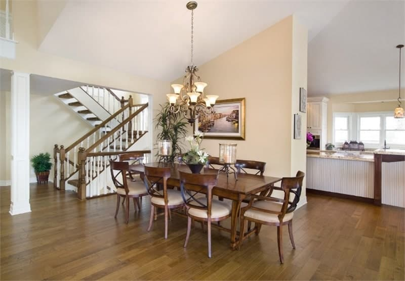 The dining room offers a long rectangular table complemented by cushioned chairs and a warm chandelier.