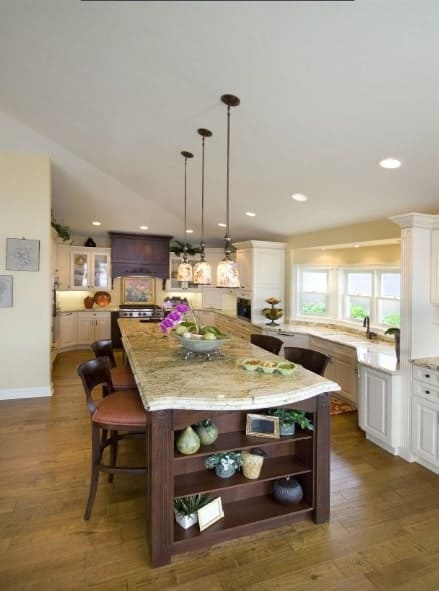 The kitchen has hardwood flooring and a vaulted ceiling mounted with glass pendants and recessed lights.