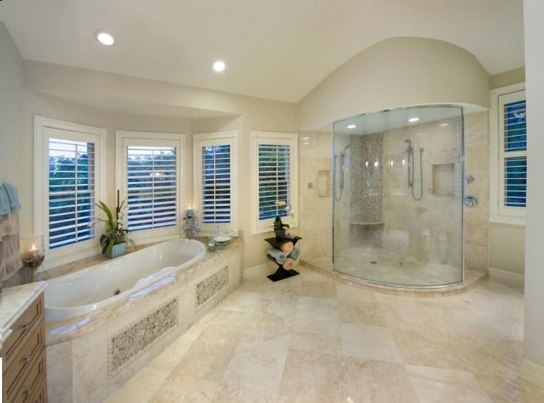 Angled view of the primary bathroom shows the deep soaking tub and a walk-in shower flanking a dark wood towel rack.