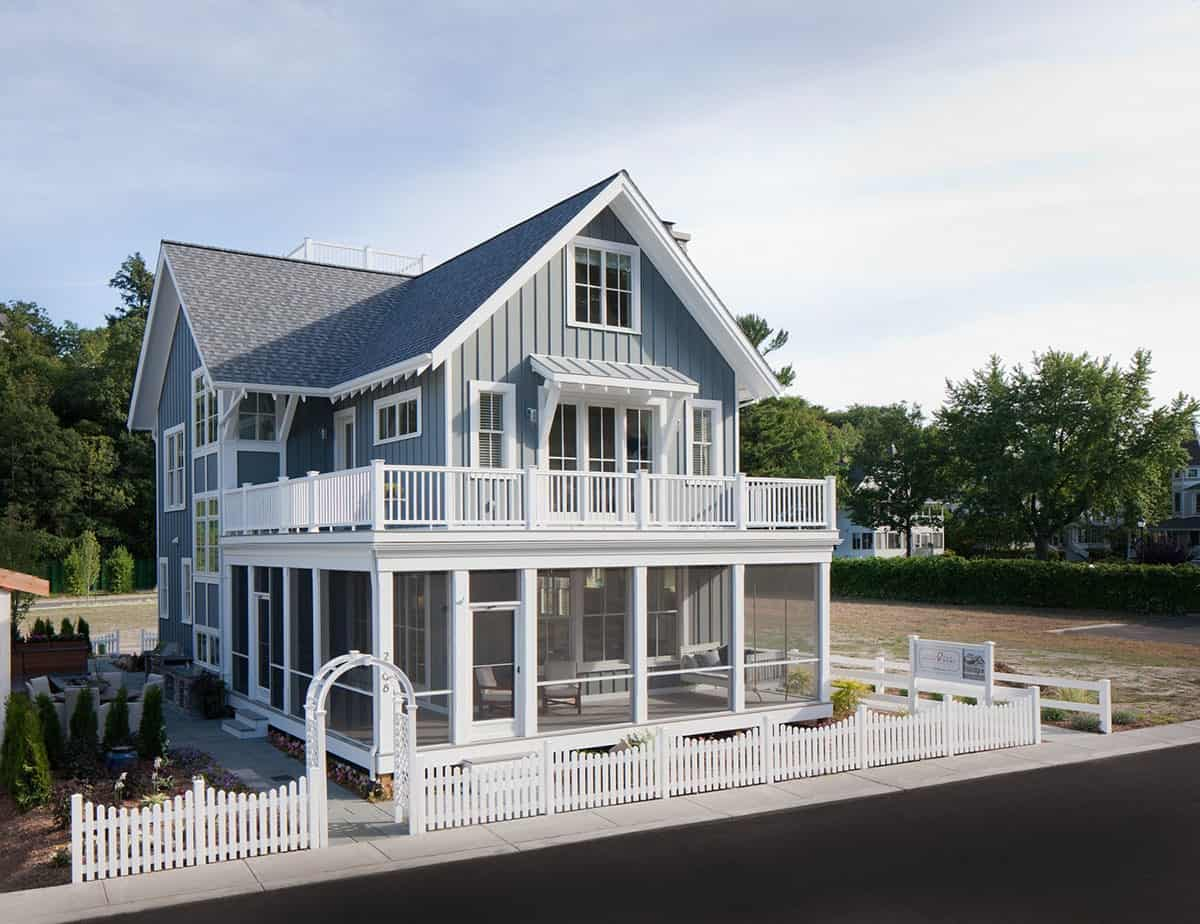 Home's facade with blue exterior siding, wraparound deck, screened porch, and white fences with an arch entry.