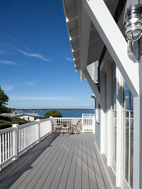 Upper sun deck with wide plank flooring and white railings overlooking the magnificent ocean.