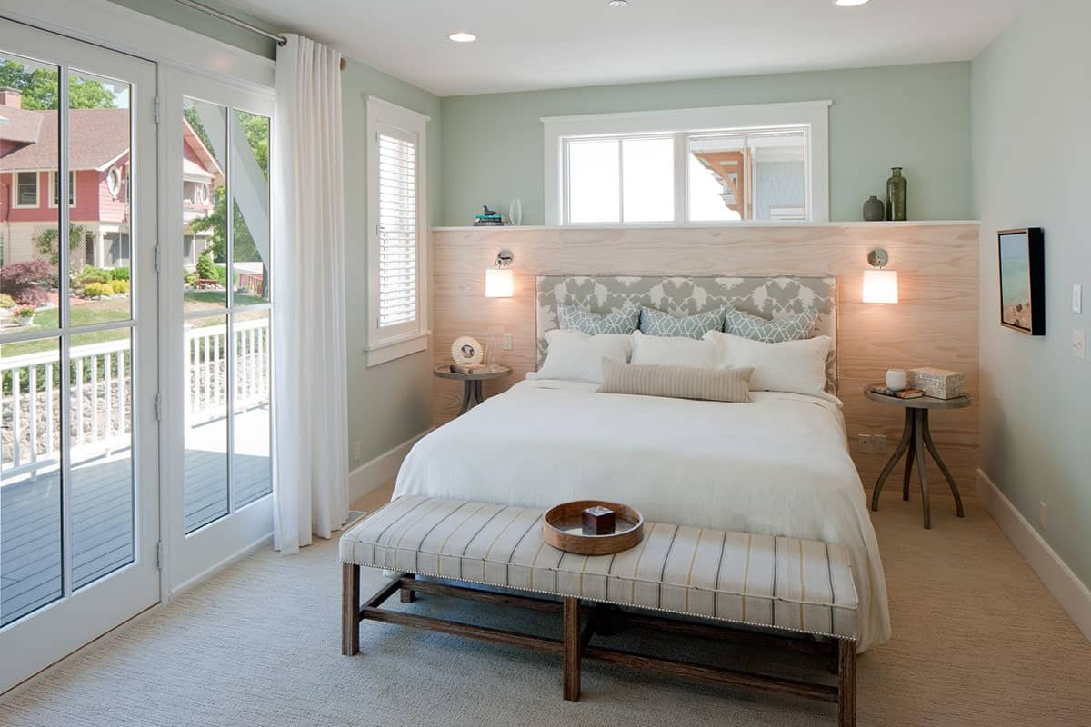 Primary bedroom with a striped bench and cozy bed flanked by round nightstands and glass sconces mounted on the wooden headboard.
