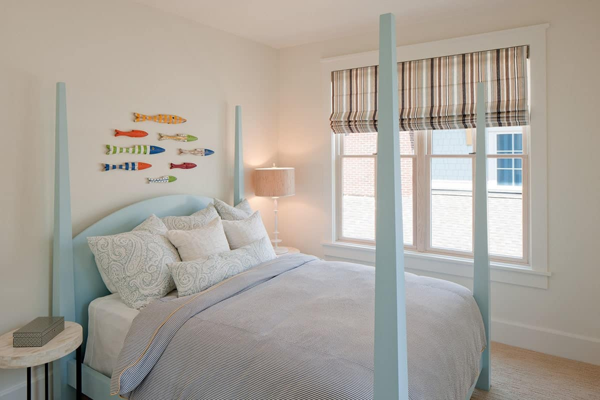 This bedroom has a blue four-poster bed and a white framed window dressed in a striped roman shade.