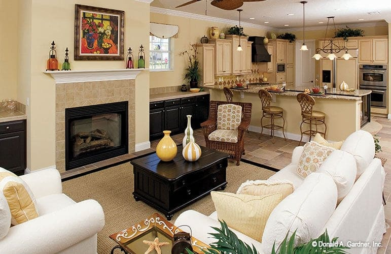 The open layout view shows the living room with cozy seats and the kitchen across flooded by ambient lighting.