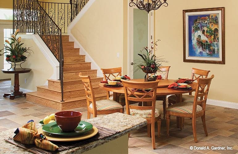 The dining area offers a round dining table and cushioned chairs over the limestone flooring.