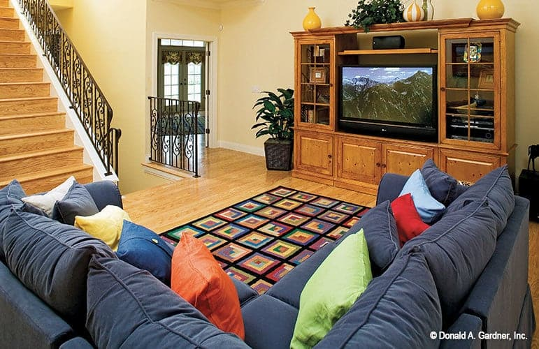 Recreation room with a TV, colorful area rug, and a blue sectional filled with multi-colored pillows.