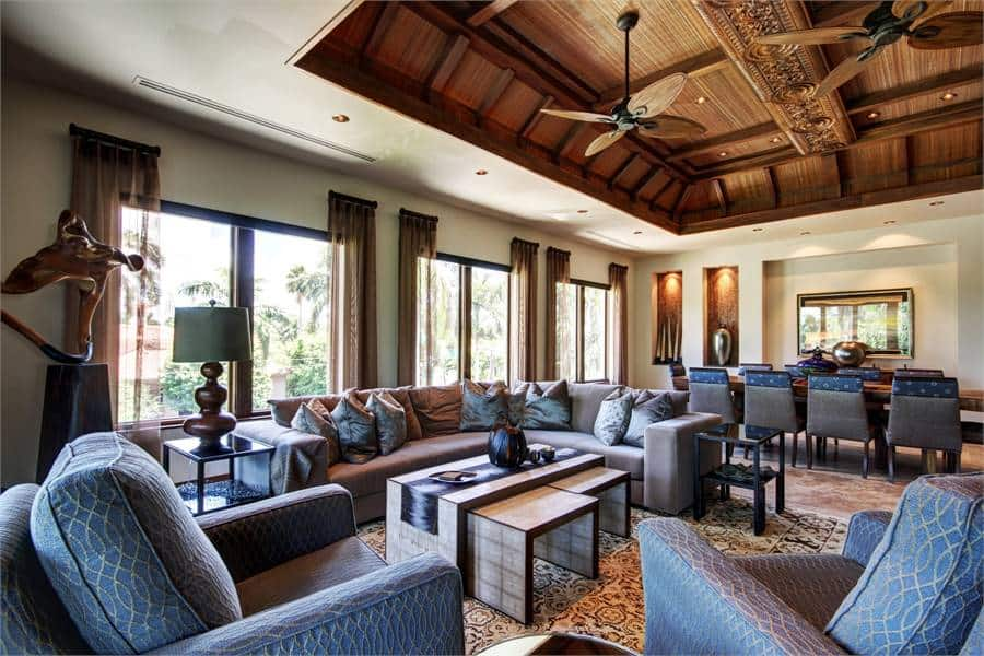 The combined living and dining has comfy gray seats and an intricate tray ceiling mounted with wrought iron fans.