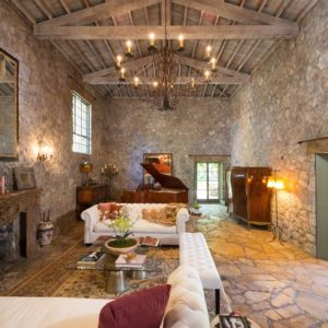 This is the large living room of the lake house with a tall wooden cathedral ceiling that has exposed wooden beams and large round chandelier. This is paired with tall textured stone walls. Images courtesy of Toptenrealestatedeals.com.