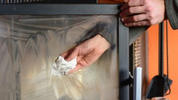 A man cleaning sooty fireplace glass with a tissue.