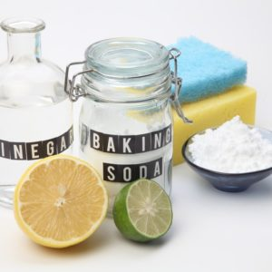 A set of natural cleaning materials like vinegar, baking soda, lemon and lime.