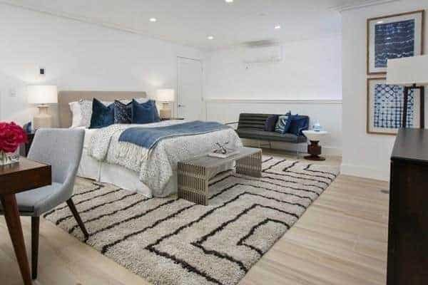 The primary bedroom has a king-sized bed on the stylish rug and white walls with wall decors.