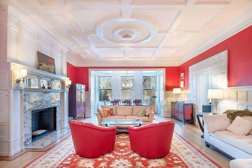 This spacious living room features a white walls with a touch of red that matches the red sofa on the red gorgeous rug.