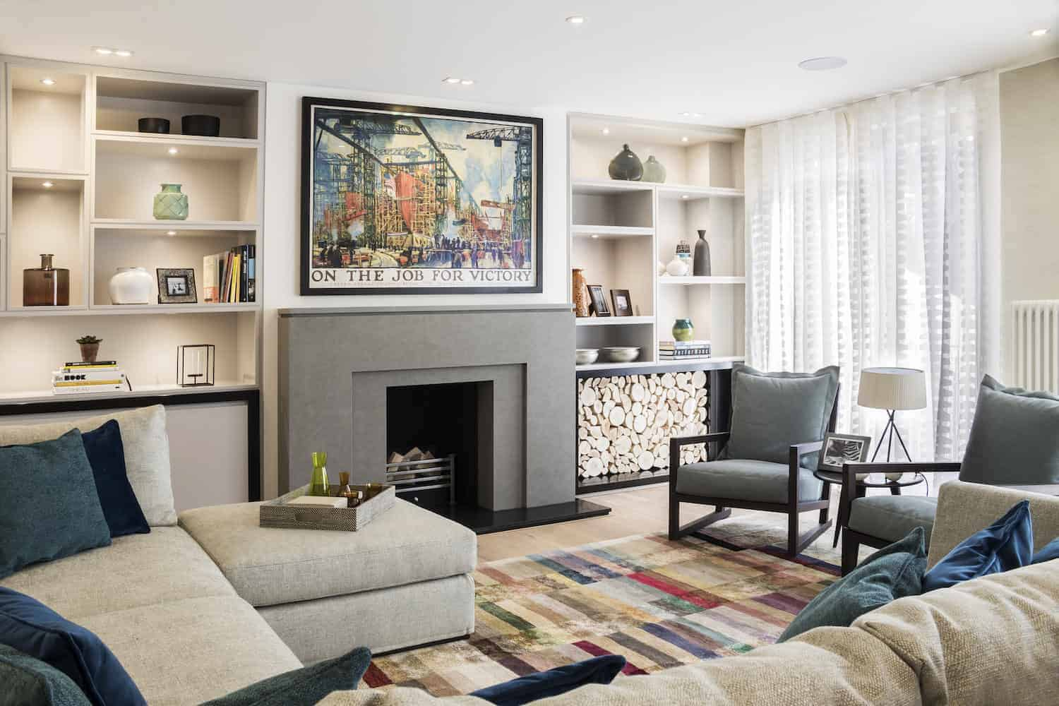 The fireplace is central to the space flanked by custom built-in shelving. The furniture includes a large, comfortable u-shaped sectional sofa facing two wood-framed accent chairs.