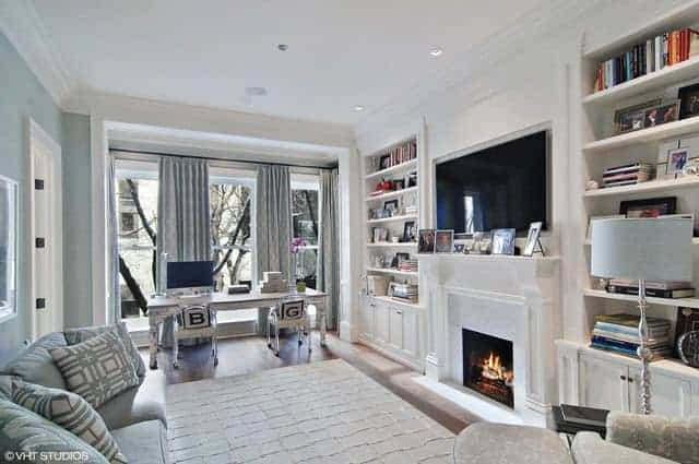 The living room has a large TV mounted on the white walls and built-in bookshelves and a classic rug on the hardwood flooring.