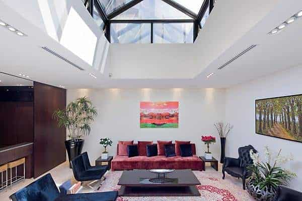 This living space has a red sofa and a wooden table on the red rug. It also has a white walls and an open high vaulted ceiling.