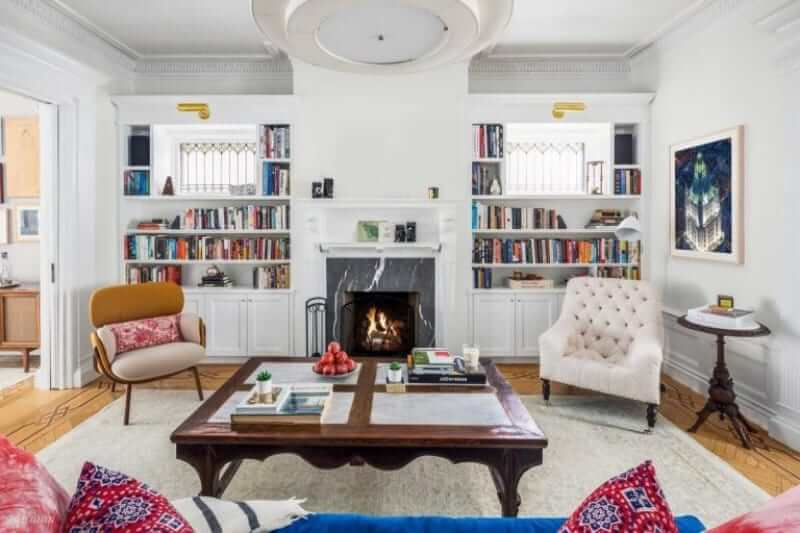 The spacious living room features a large wooden table on the stylish carpet and a fireplace that warms the area.