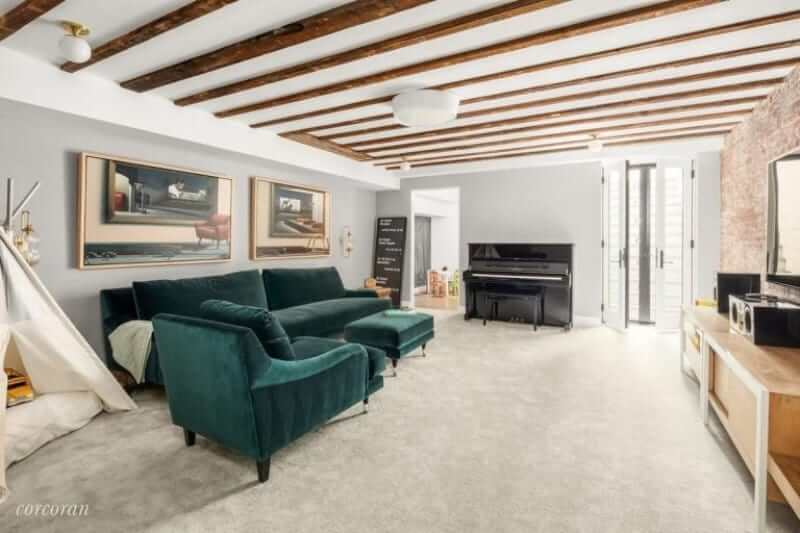 This living room features a green cozy couch on the beige carpet flooring and a high vaulted ceiling with exposed wooden beams.
