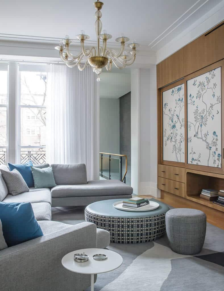 There is a large area rug which matches the furniture. Designs on the ottoman and the wall panels, along with the colors of the accent pillows help to add life to space.