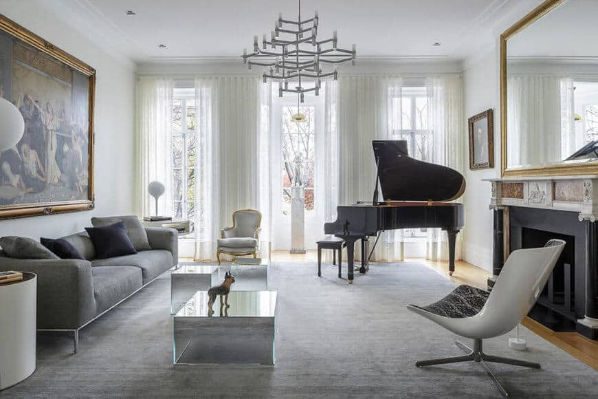 This room also features both modern and historic themed furniture, as well as a large piano set next to the windows. Natural light reflects off multiple surfaces in this space.