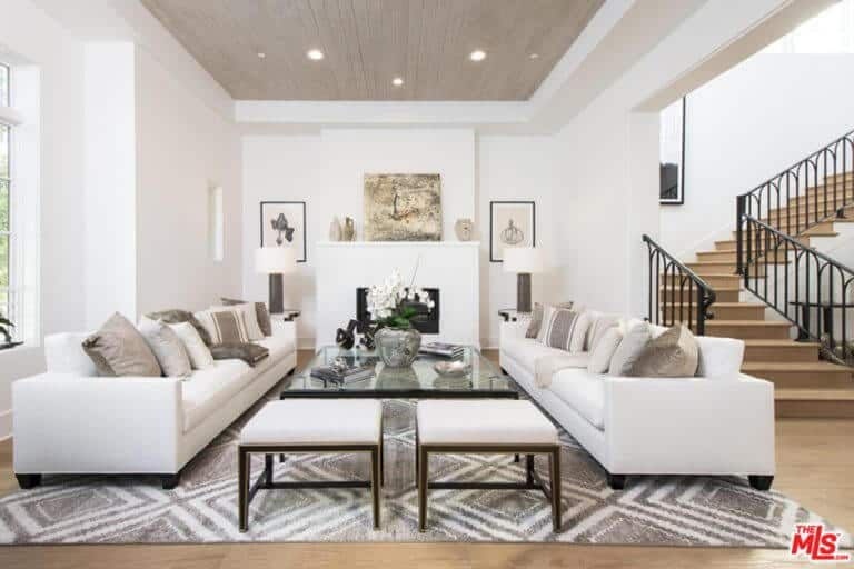 This living space features cozy white couches and a glass table on the stylish rug. It also has a white walls and that match the hardwood flooring.