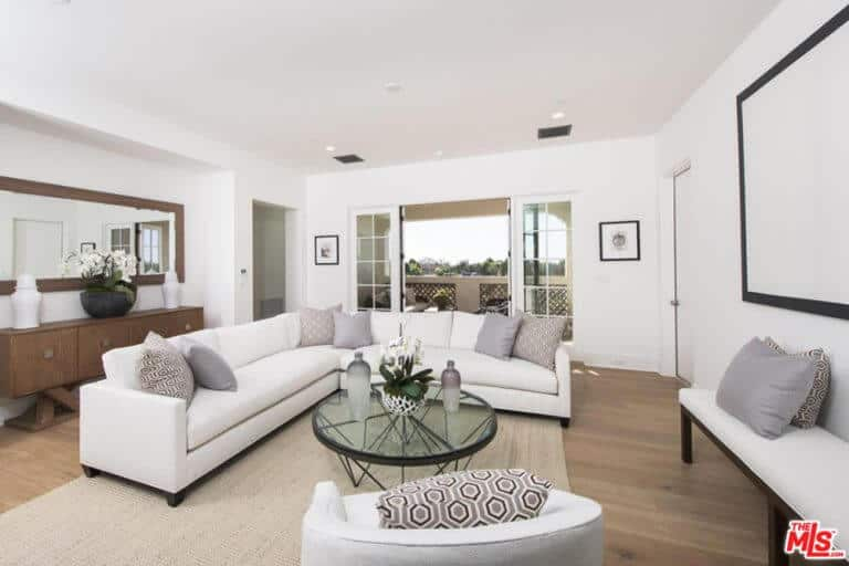 An L-Shape white couch and glass circle table on the brown carpet. There's a doorway that leads to the balcony.