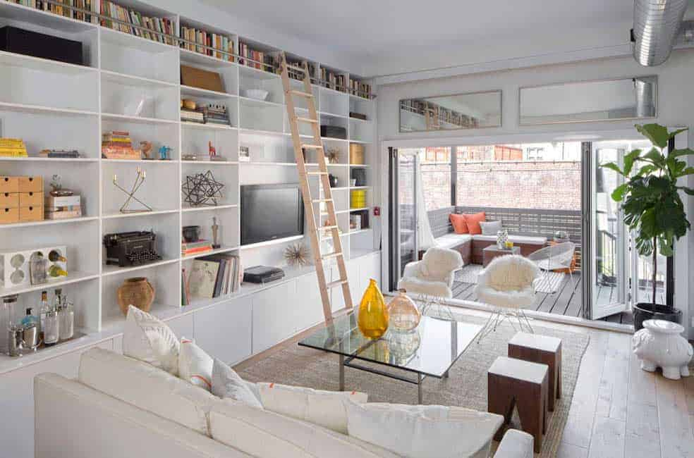 This living room features a cozy couch and glass table on the rug and built-in bookshelves with a wooden rolling ladder.