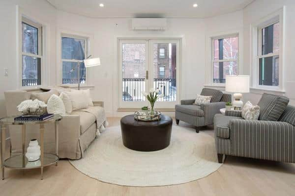 This contemporary living room has a cozy couch and a white walls and ceiling with recessed lights.