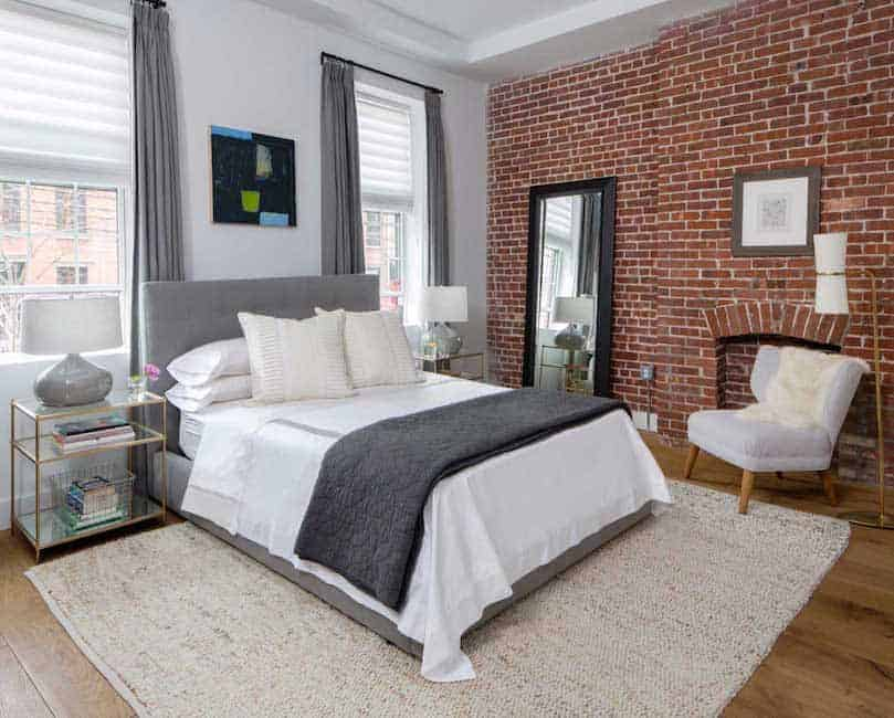 This primary bedroom features a brick wall that matches the hardwood flooring and a comfy bed with a grey headboard on the carpet.