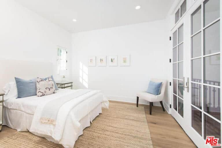 The primary bedroom has a white comfy bed on the stylish rug and white ceiling with recessed lights.