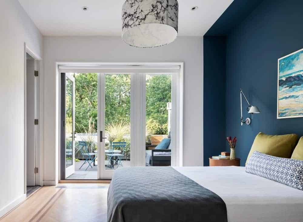 This primary bedroom has a blue wall with wall painting and a glass door that leads to the balcony. It also has hardwood flooring and drum pendant lights.