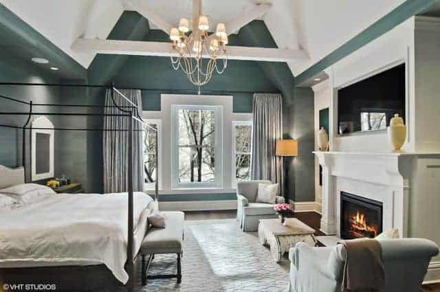 This primary bedroom features a high vaulted ceiling exposed with wooden beams and luxurious chandeliers. The fireplace warmth the bed space.