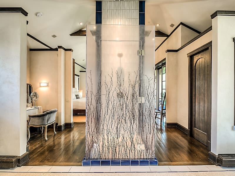 This is the glass enclosed shower area of the primary bedroom with lovely frosted glass panels adorned with plant-like designs. Images courtesy of Toptenrealestatedeals.com.